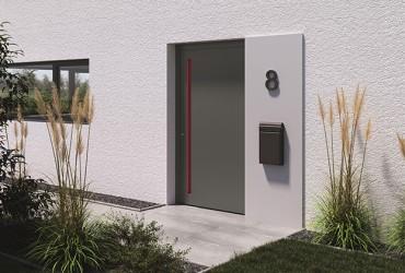 Le Corbusier Haustuer - weiss verputzte Hauswand mit grauer Haustuer und roter Griffmulde
