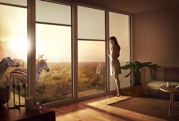Designvielfalt-Frau neben Fenster mit Sonnenschutz