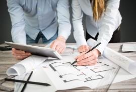 Architektenberatung-Ausschreibungstexte-zwei Architekten mit Plaenen auf Schreibtisch
